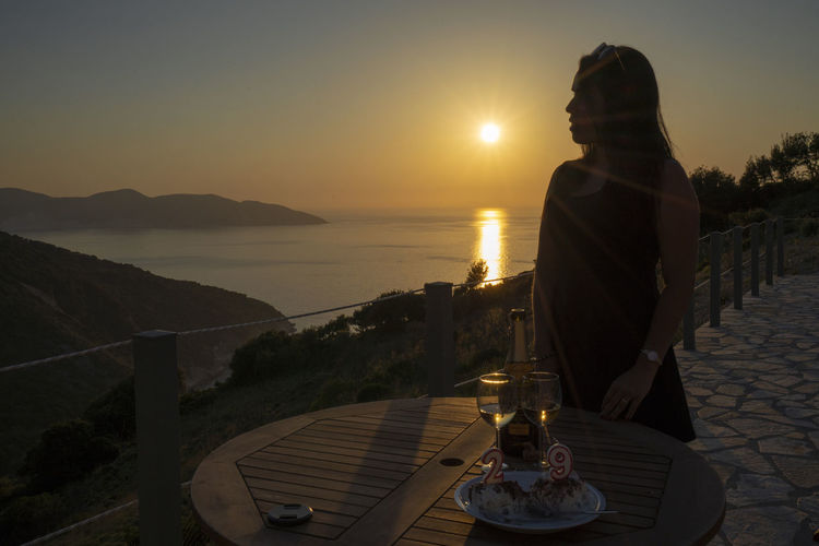 Woman sitting on table by sea against sky during sunset
