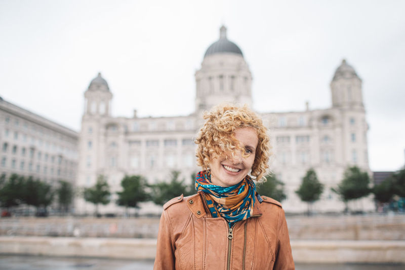 Portrait of smiling woman standing against buildings in city