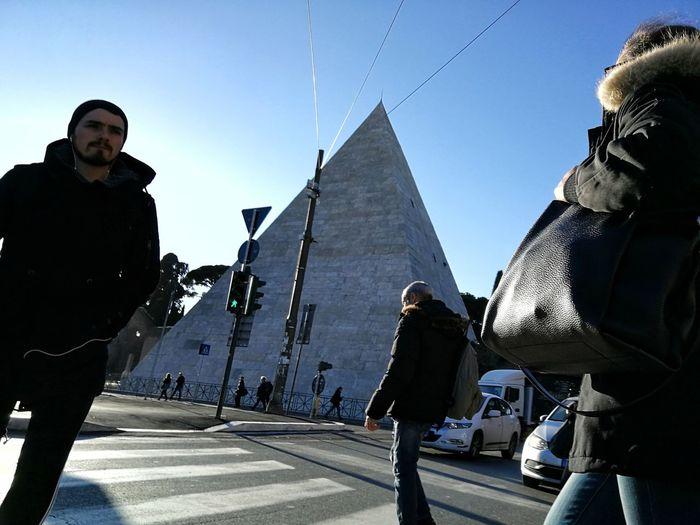 Men walking in city against clear sky