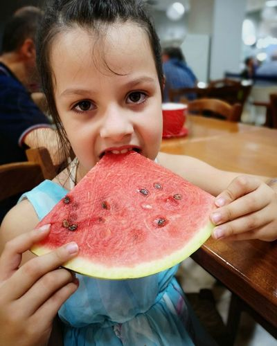 Portrait Of Girl Eating Watermelon On Table