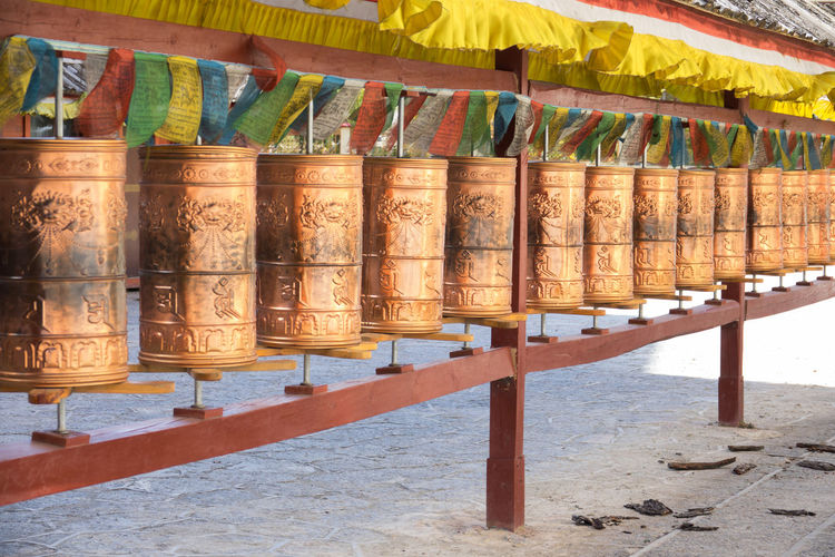 Golden praying wheels, Tibetan buddhist symbols Architecture In A Row Day No People Place Of Worship Built Structure Belief Religion Spirituality Nature Sunlight Side By Side Multi Colored Outdoors Arrangement Wood - Material Hanging Building Architectural Column Shrine China Tibet