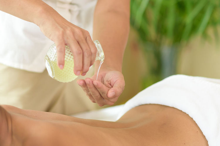 Midsection of therapist pouring massage oil by woman lying at health spa
