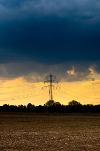 Silhouette electricity pylon on land against sky during sunset