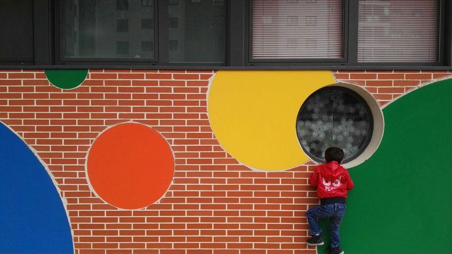 Full length of boy looking through circular window of building