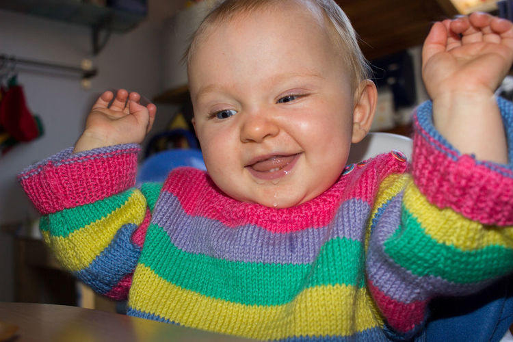 little child in colorful sweater sitting at kitchen table cheering Kitchen Home At Home Home Interior European  Caucasian Caucasian Ethnicity Blue Eyes Blue Toddler  Toddlerlife Baby Babyhood Cute Sweet Adorable Child Childhood Sitting Looking At Camera Front View Real People Indoors  Blond Hair Blonde Blond Human Face Portrait Innocence Indoors  Colorful Pullover Knitted Sweater Arms Raised Happy Happiness Funny Funny Faces One Person Smiling Emotion Cheerful Close-up Casual Clothing Focus On Foreground Warm Clothing Cheering