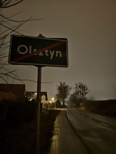 Road sign by street against sky in city