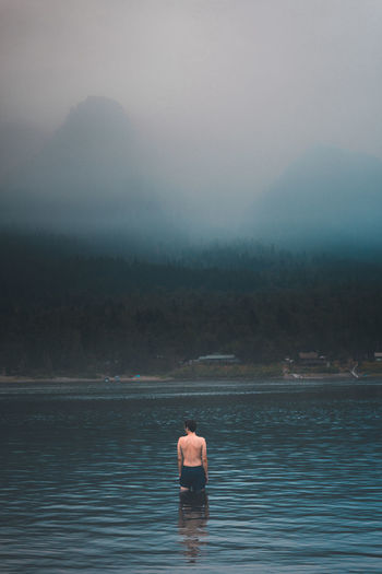 Rear view of man sitting on lake against sky
