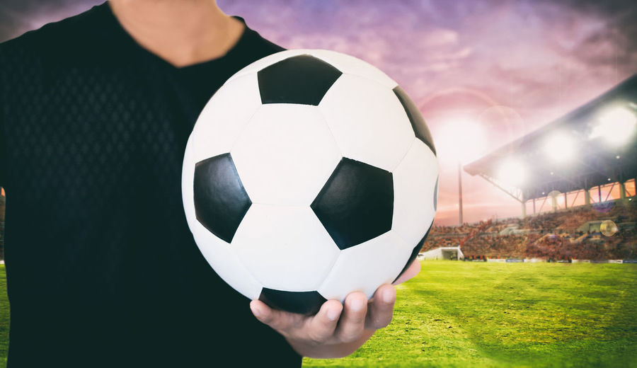 Midsection of man holding soccer ball on field