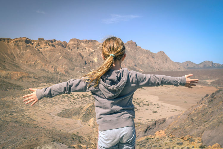 Rear view of girl with arms outstretched standing at desert