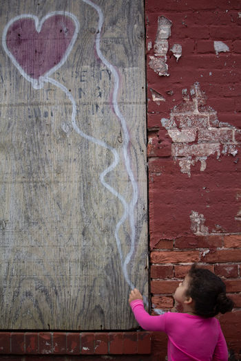 Girl drawing on wooden wall