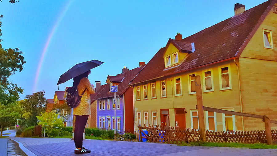 A Girl Calling Out The Rainbow Built Structure Building Exterior Architecture Sky One Person Umbrella Real People Building Day Nature Clear Sky Protection Lifestyles Full Length Standing Women Leisure Activity Security Outdoors Rain Rainbow Colors Girl Afternoon Afteroon Sun Backgrounds Background Wallpaper Wall Wall Art Germany
