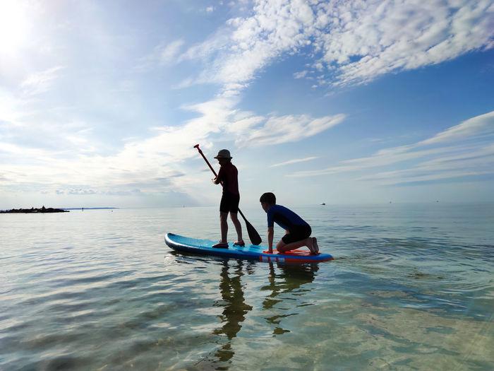 Siblings paddleboarding on sea against sky