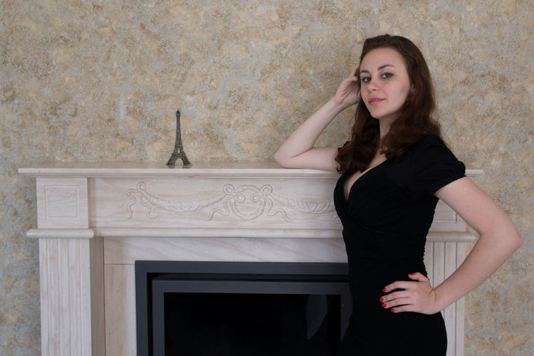 Portrait of young woman posing by eiffel tower replica on fireplace mantel at home
