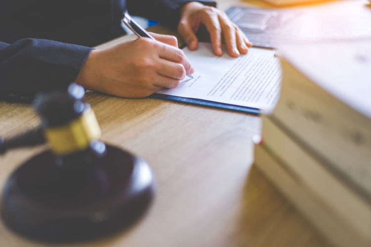 Midsection of female lawyer writing on paper at desk