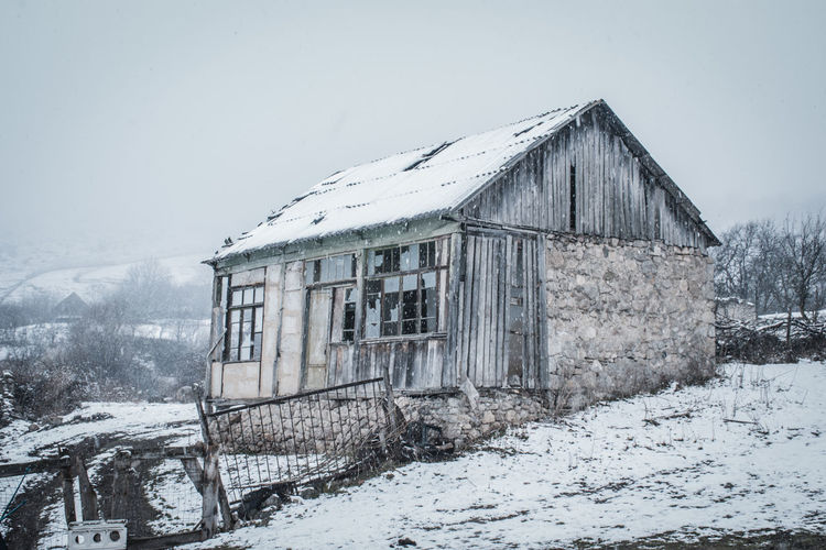 Abandoned house against sky during winter