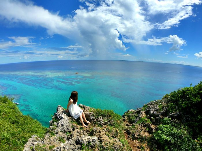 High angle view of woman sitting on rock over sea against sky