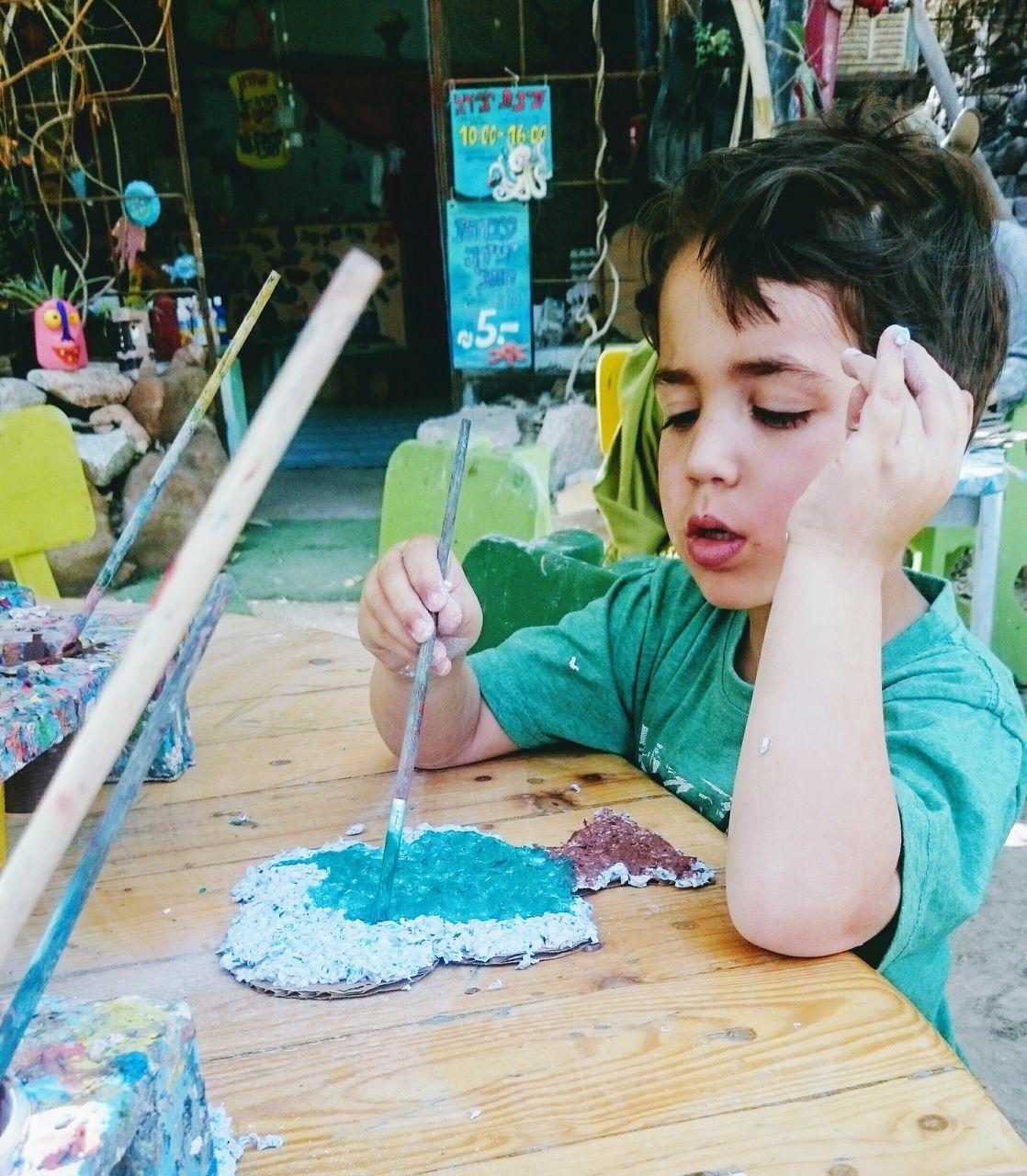Boy Painting Artwork At Table