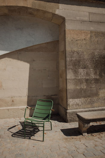 Empty chair against wall in abandoned building