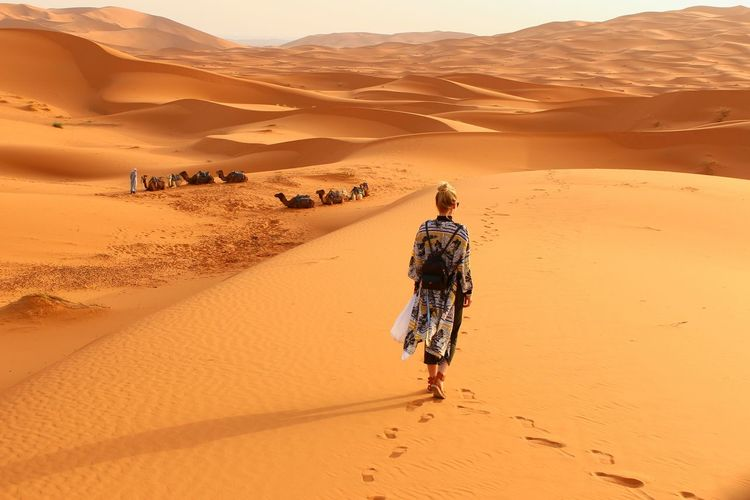 Rear view of woman walking in desert