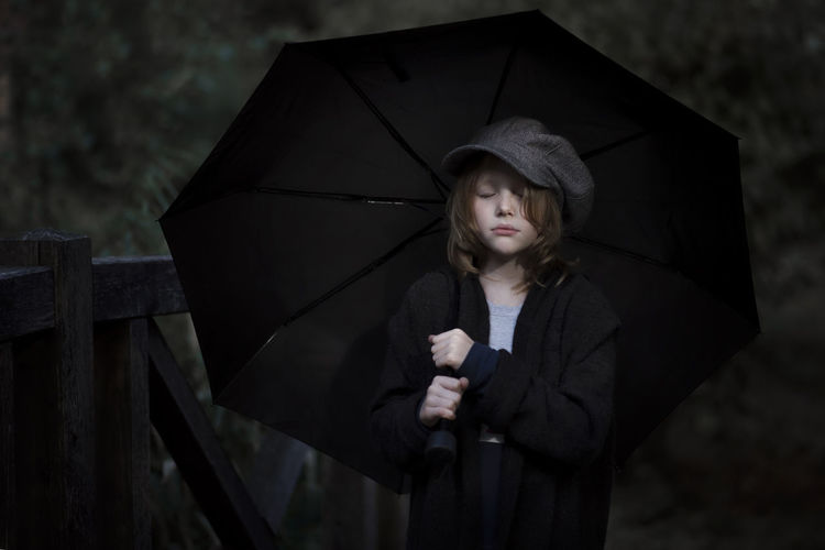 Girl holding umbrella standing in rain during rainy season