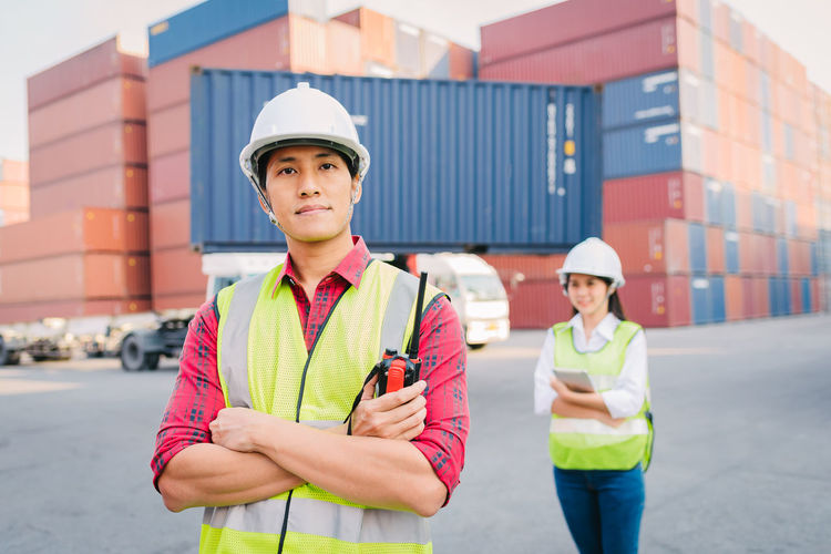 Portrait of manual worker with colleague standing against cargo containers