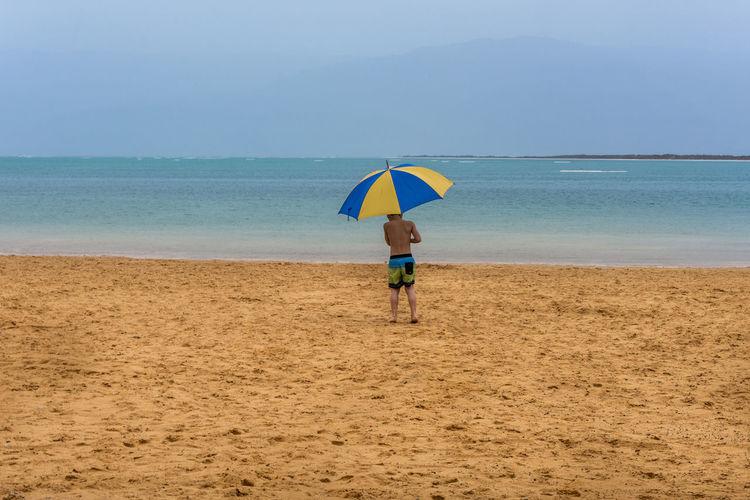 Boy holding sunshade on beach