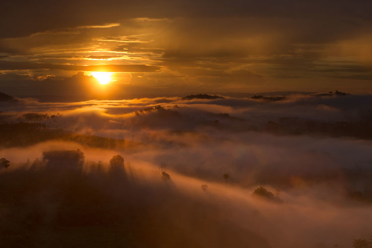 Scenic view of landscape in foggy weather against sky during sunset