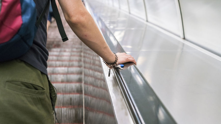 Midsection of woman standing on escalator