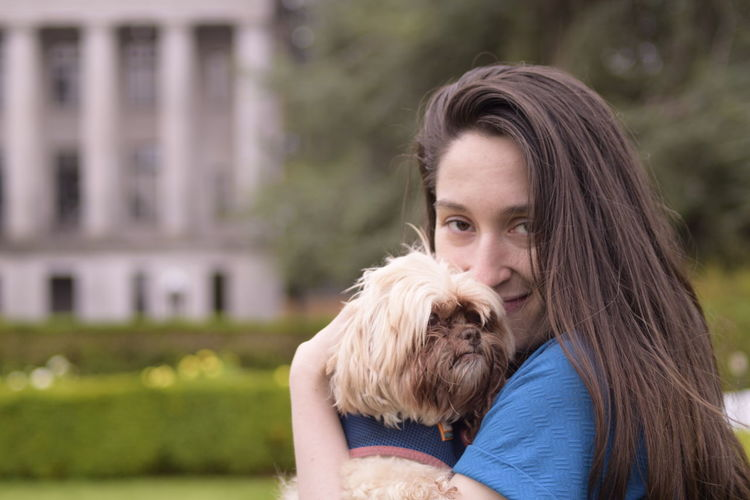 Portrait of woman carrying dog in park