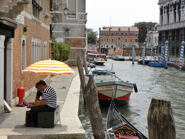 Venice, Italy Canal Gondola Gondolieri Taking A Break Waiting For Customers Taking A Rest  Having A Chat Under The Umbrella  Sun Umbrella In The Shade in Venice
