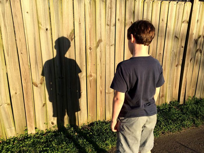our lives are moving shadows that we wonder at until the sun sets. Black Boy Brown Casual Clothing Day Ephemeral Fence Fencing Friendship Learn & Shoot: Balancing Elements Moment Person Rear View Shadows Silhouette Standing Tan Togetherness Wood Live For The Story