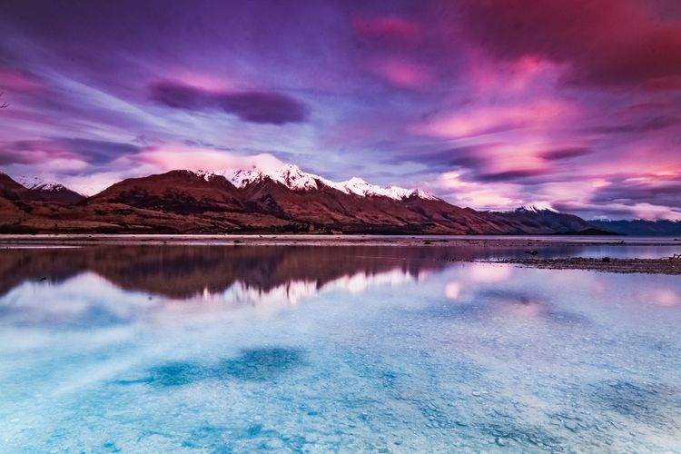 Scenic View Of Calm Lake And Mountains Against Dramatic Sky