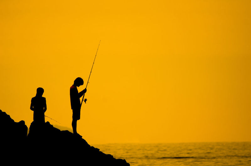 Silhouette people fishing in sea while standing on rock against clear sky during sunset