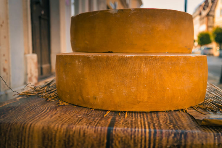 large cheese loaves on a wooden table Art And Craft Cheese Cheese Wheels Close-up Day Focus On Foreground Food Food And Drink Freshness Household Equipment Indoors  No People Old Simplicity Stack Still Life Table Wellbeing Wood - Material Yellow