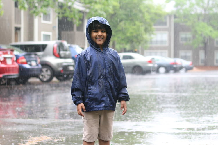 Portrait of smiling boy standing on wet city street during rainy season
