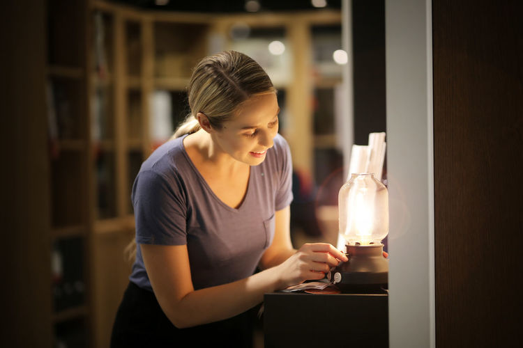 Smiling woman adjusting flame of oil lamp at home
