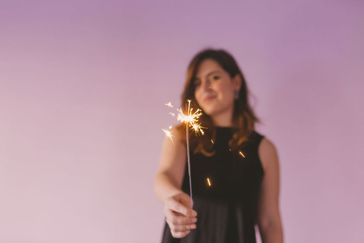 Lighting Caucasian Fun Year Young Light Holiday Sparkler Season  Happy Festive Female Decorated Indoors  Home New Lifestyle Attractive Illuminated Sparkle Cute Celebration Sweater Bengal Beautiful Inside Happiness Smile Firework Little Style Pretty Magic Beauty House Studio Woman Girl Casual Purple Background Wall Ultraviolet Women Isolated One Concept