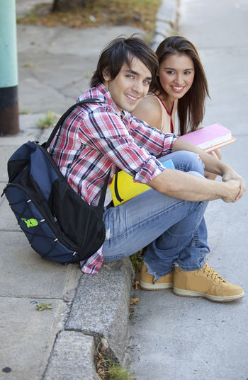 Portrait of smiling friends sitting on footpath