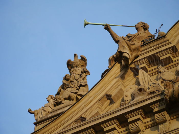 Low angle view of ornate building exterior with angels