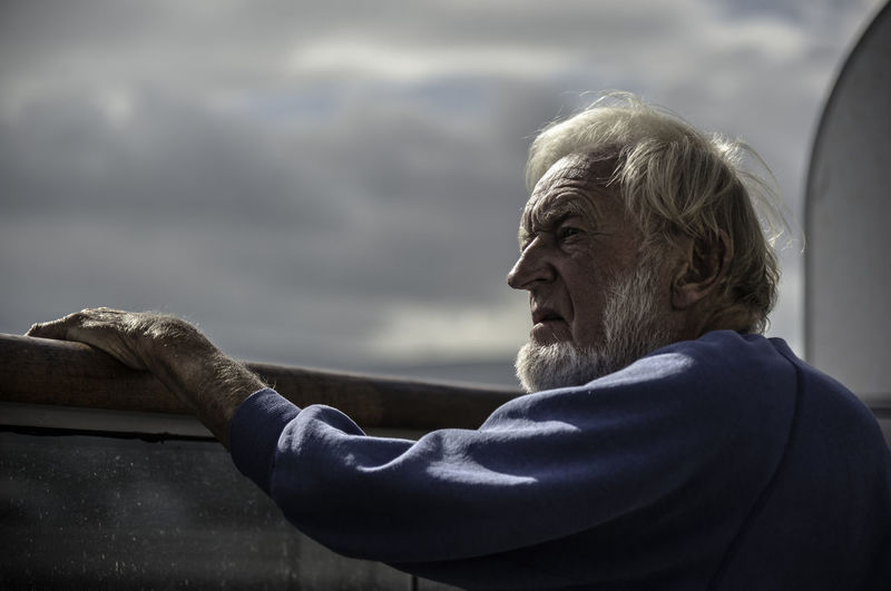Side view of senior man looking away while standing by railing in boat