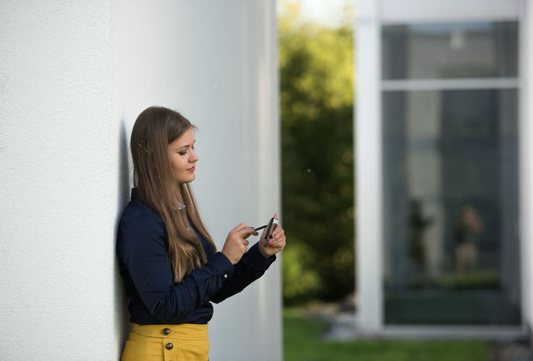 Side view of smiling young woman using mobile phone by concrete wall