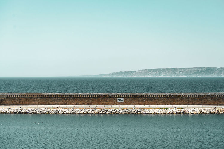 Marseille harbor wall , ocean and mountain Sea Water Nature Sky Blue Day Outdoors Tranquility Horizon Waterfront Clear Sky Beauty In Nature No People Idyllic Copy Space Tranquil Scene Non-urban Scene Horizon Over Water Salt Flat Turquoise Colored Hoffi99 Scenics - Nature