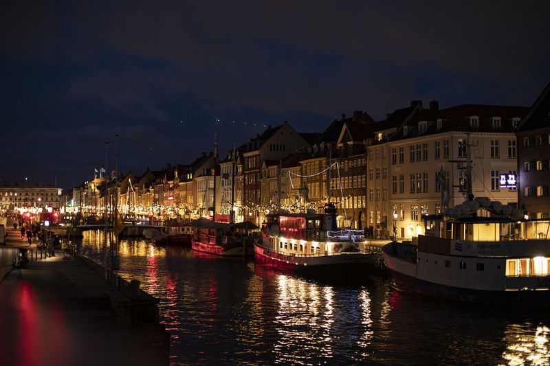 Sailboats moored on river by illuminated buildings in city at night