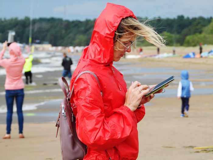 Midsection of woman holding mobile phone while standing on land