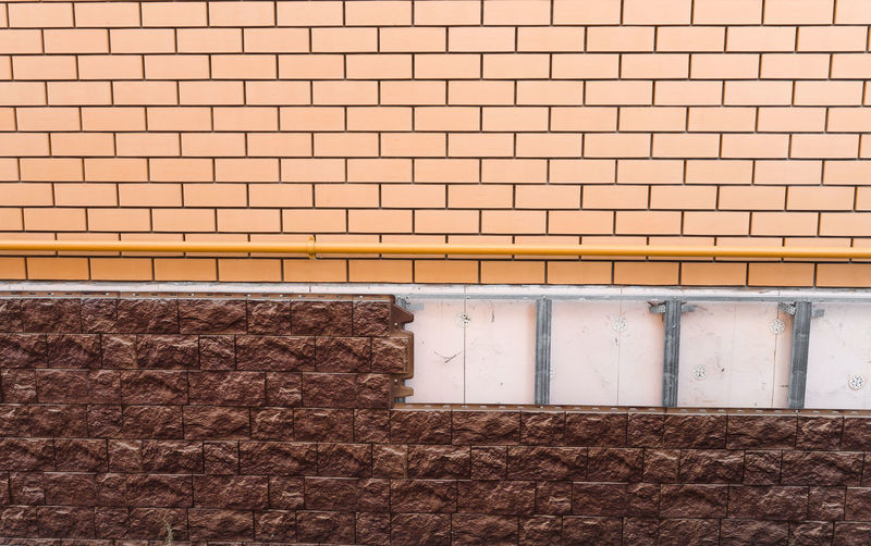 Brick wall and masonry applied to the facade of a building, house construction.