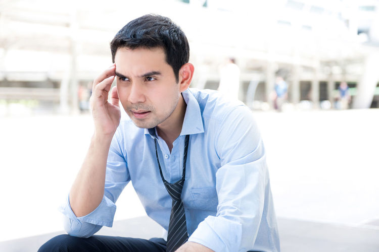 Frustrated businessman sitting outdoors