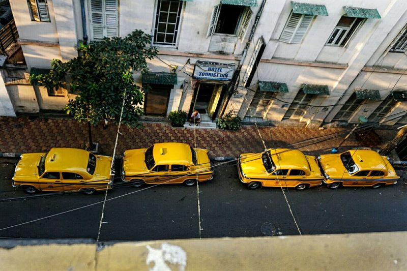 Vintage cars line the streets of Kolkata in the rising sun April Showcase India Vintage Cars Yellow On The Way The Journey Is The Destination Bird's Eye View
