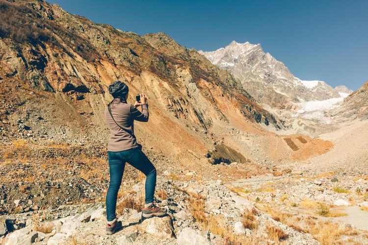 Full length rear view of man walking on rock against sky