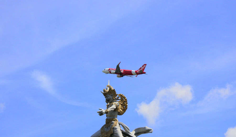 catch me if you can Sky Air Vehicle Low Angle View Flying Airplane Nature Blue Day Mode Of Transportation No People Motion Mid-air Cloud - Sky Representation Transportation Sculpture Art And Craft Travel Outdoors Statue Plane Arms Raised Staue  Bali Indonesia A New Beginning