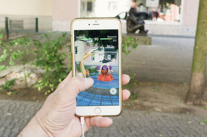 BERLIN, GERMANY - JULY 21, 2016: Pokemon Go game app on an iPhone in Berlin, Germany as the augmented reality app was recently released by Nintendo for the German market. App Augmented Reality Catching Cell Phone Photography Connected Fun Gaming Go Hand Hunting IPhone Leisure Mobile Niantic Nintendo Online  Outdoors Playing Pokemon Go Pokémon Smart Phone Social Gaming Street Success Virtual Reality